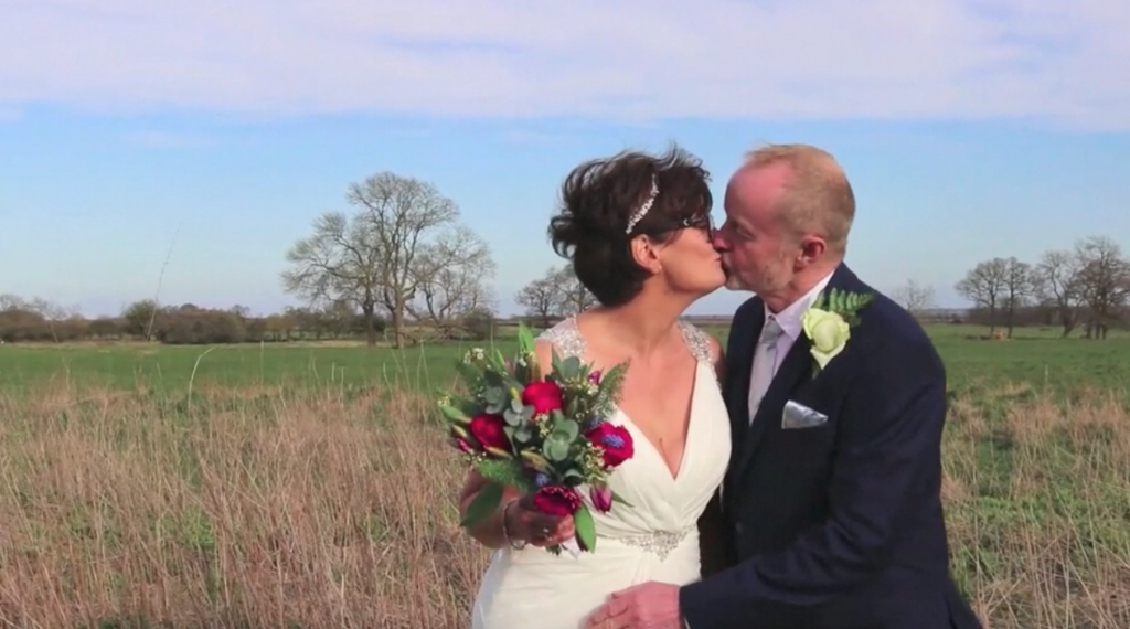 Bride and Groom kissing in field in Leicester with sunset in background